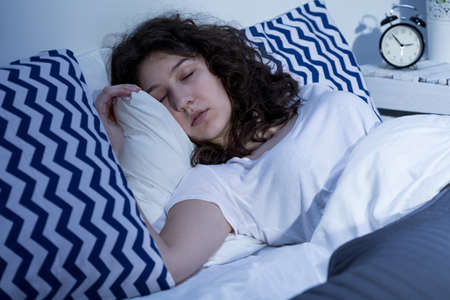 cosy: Close+up of young woman sleeping in cosy bed Stock Photo
