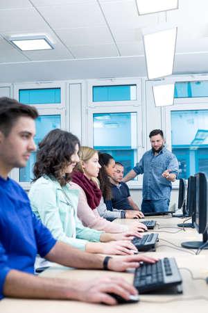 De leraar verklaart iets met de toezegging aan de deelnemers computer cursus