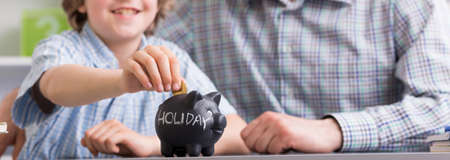 teach: Black piggy bank- saving money at young age Stock Photo