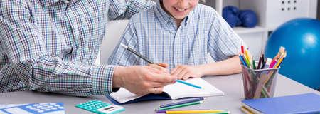 tarea escolar: Padre ayudando a su hijo con la tarea en el mostrador Foto de archivo