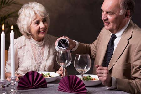 anniversario matrimonio: Uomo anziano, versare il vino rosso per la sua bella moglie elegante durante la cena anniversario di matrimonio Archivio Fotografico