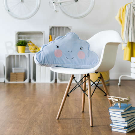 Infantile cushion lying on white chair standing in new, spacious room Stock Photo