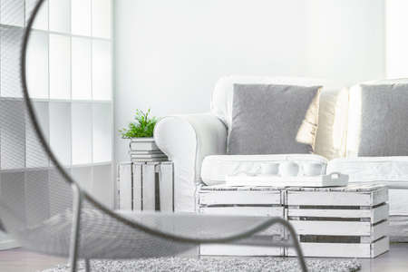 lightsome: Living room with fancy chair, couch and coffee table made from recycled materials