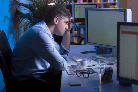 night shift: Shot of a resigned office worker sitting in front of his computer at night Stock Photo