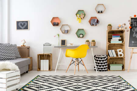 room decor: Spacious white cozy teenager room designed in scandinavian style. On the floor carpet in white and black pattern
