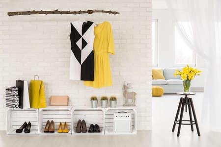 Lichte hal met recyclebare meubels, grenzend aan een grote woonkamer met veel ramen Stockfoto