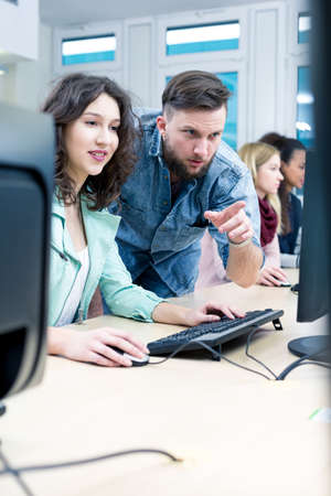 schoolmate: During IT lessons teacher points something to female student on a computer screen Stock Photo