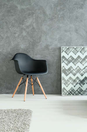 radiantly: Part of room with modern chair and interesting geometrical painting Stock Photo