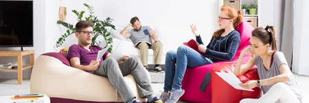 persona sentada: Disparo de un grupo de estudiantes que leen sus notas en una moderna sala con pufs