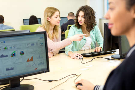 computer science: Computer science lesson with young girls talking to each other Stock Photo