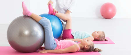 corrective: Two girls exercise on rubber balls placed on the mats
