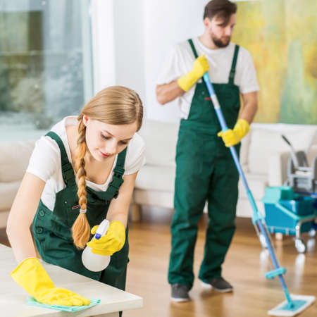 Cleaning team: Young professional cleaners cleaning accurate spacious apartment. Man mopping the floor and girl polishing the table