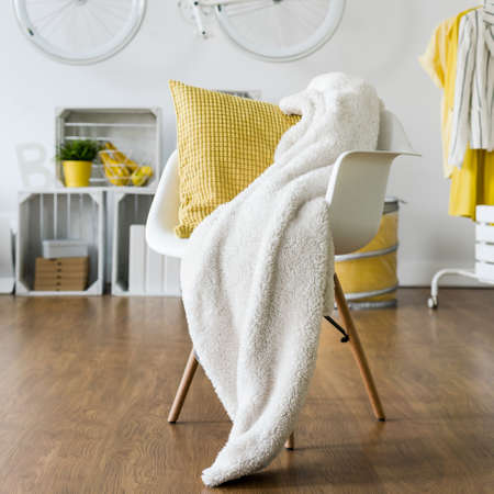white pillow: Yellow pillow and white blanket left on white armchair in lounge