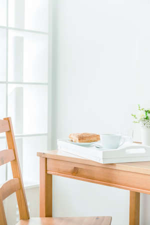 eating area: Eating area in a bright and calm room. On the table are a tray and plant
