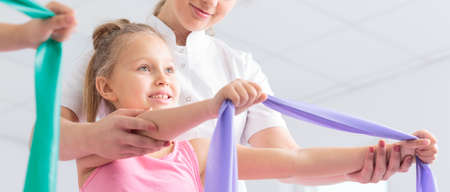 femal: Femal physical therapist helps a girl which is holding in hands rubber band