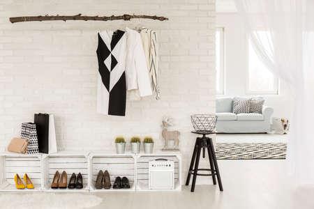Jonge vrouw hal ingericht in zwart en wit, met recyclebare meubels en kleding, grenzend aan een lichte woonkamer Stockfoto
