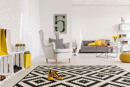 Zeer ruime woonkamer in het wit, met gele decoraties en schoenen met hoge hakken in het midden van een modern tapijt Stockfoto