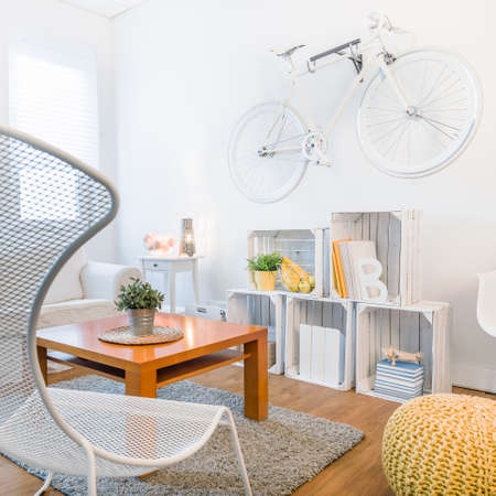 original bike: Cozy students studio with modern stylish decor. Fancy armchair and wooden coffee table in living room Stock Photo