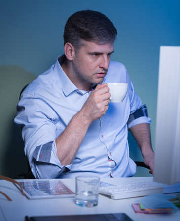night shift: Shot of a middle-aged businessman staying late in his office and drinking coffee