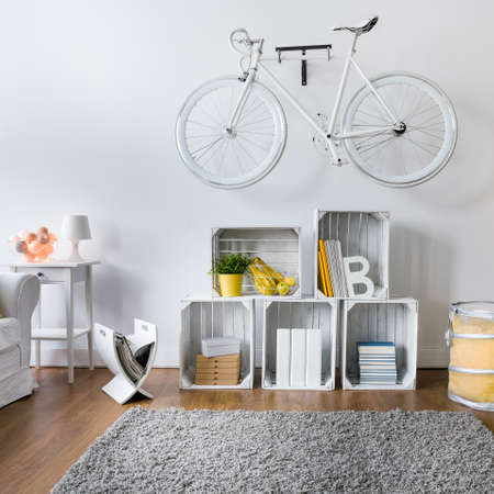 original bike: Modern living room with white stylish bicycle hanging on wall