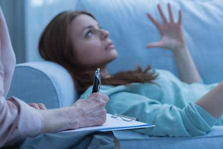 overwhelmed: Closeup of a therapist taking notes about her overwhelmed patient Stock Photo