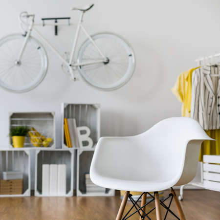 original bike: Close-up of white armchair in spacious living room. In the background wooden shelf and bicycle hang on wall