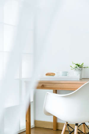 quite: Quite and calm part of a bright room with a wooden table and white chair