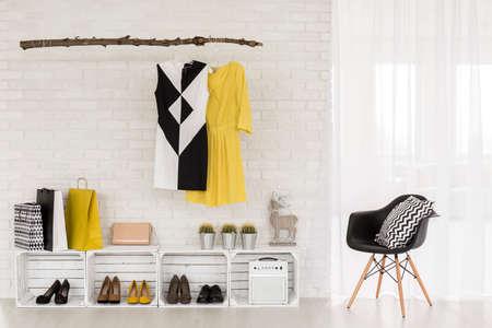 Fragment van een moderne flat met schoenenrek en kleerhanger gevuld met modieuze items van de vrouw