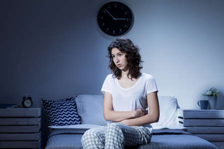 Woman with stomach pain sitting on bed at night