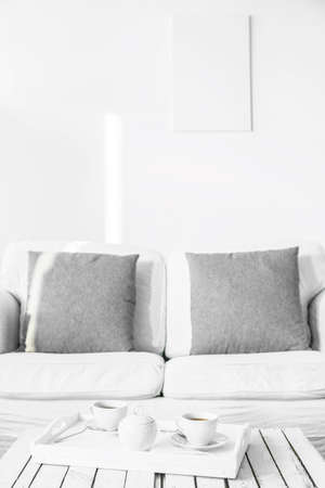 lightsome: White, comfortable couch and coffee table in a bright room