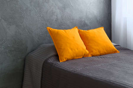 radiantly: Part of bedroom with bed placed at the gray wall
