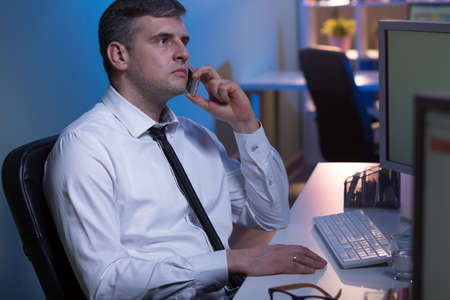 night shift: Shot of a focused office worker talking over the phone Stock Photo