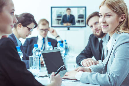 formally: Group of formally dressed people gathered around a conference table, with a smiling woman in the foreground Stock Photo