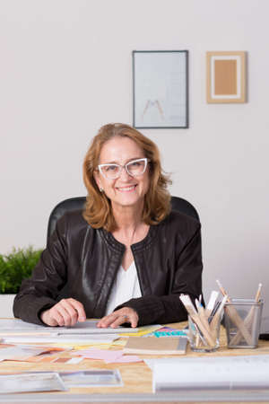 interior designer: Shot of a smiling interior designer sitting at her desk and looking at the camera