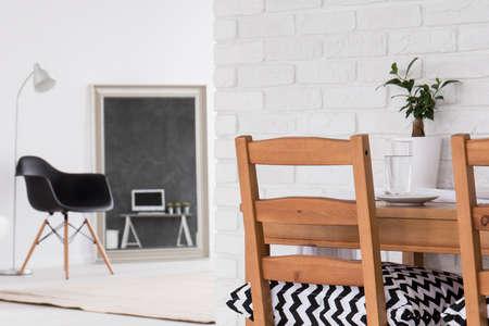 silla de madera: espacio multifuncional blanco con espejo grande y una mesa de comedor
