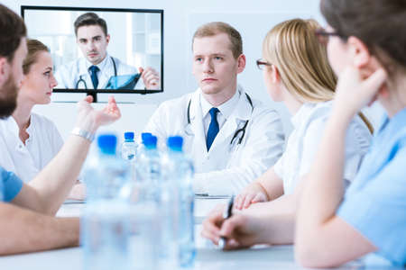 md: Young doctors sitting around a conference table and communicating on-line with a doctor displayed on a tv screen Stock Photo