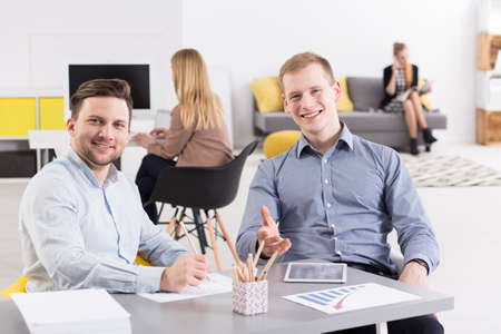 open space: Shot of smiled men workers sitting at a desk in a spacious open space Stock Photo