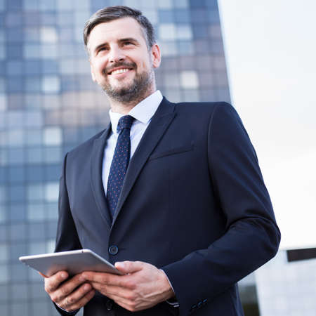 headquarters: Photo of handsome manager standing outside headquarters of firm