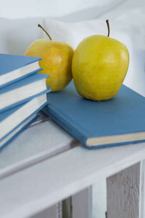 Closeup of a white wooden table with apples and books with blue covers