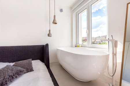cropped shot: Cropped shot of a spacious bathtub standing by a window in bedroom