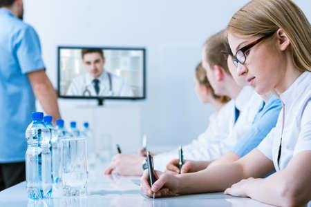 online conference: Close-up of a young woman doctor taking notes during an on-line conference in a blurry, bright conference room Stock Photo