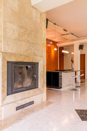 stone fireplace: Stone fireplace in a vast house interior, with kitchen island in the background