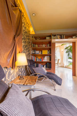 reading room: Reading room in safari style with two lounge chairs and a fitted bookcase