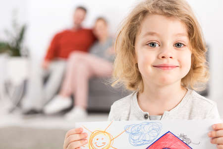 couch: Smiling boy is holding in his hand his drawing Stock Photo