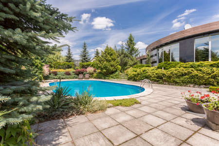 Luxurious swimming pool in the garden of an extravagant detached house Stock Photo