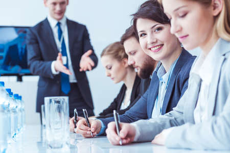 group strategy: Female corporate staff member smiling at the camera while taking notes at a conference table, surrounded by her colleagues