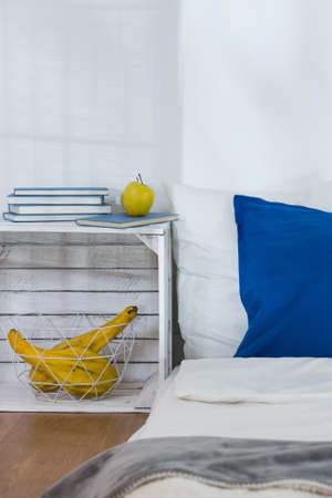 night table: Cropped shot of a stylish interior with a bed and handmade night table Stock Photo