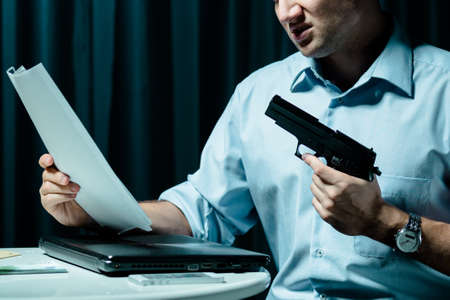 Shot of a contract killer holding a gun and reading documents
