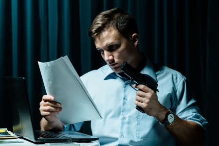 Shot of a focused man holding a gun and reading some files