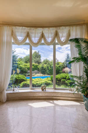 vast: Panoramic window with decorative curtains overlooking vast garden with swimming pool